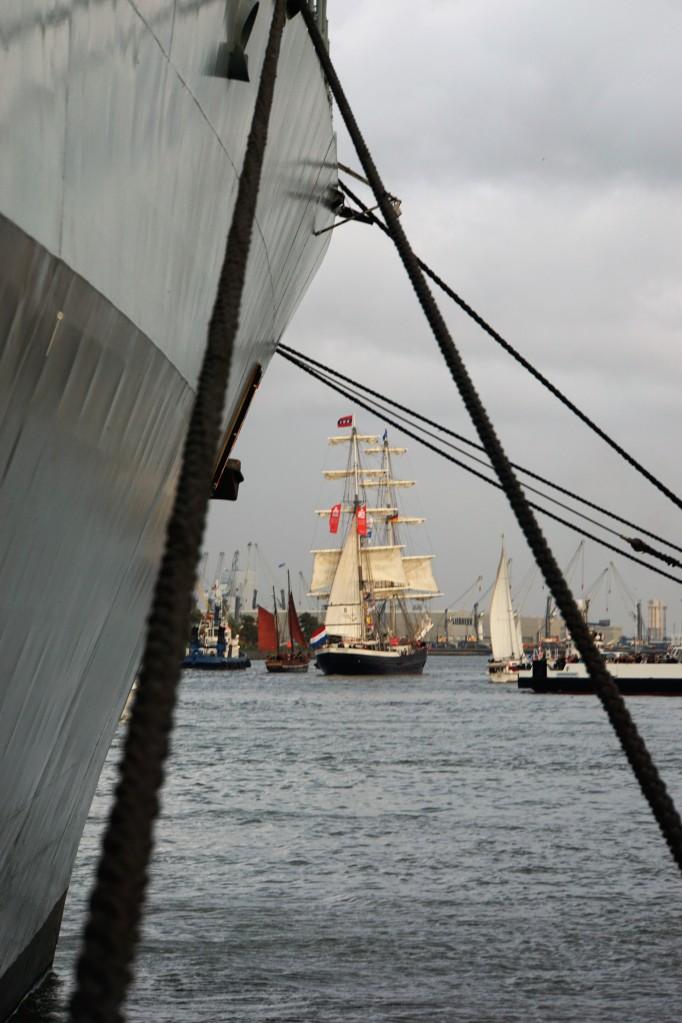 Ein festgemachtes Schiff, ein Segelschiff im Hintergrund